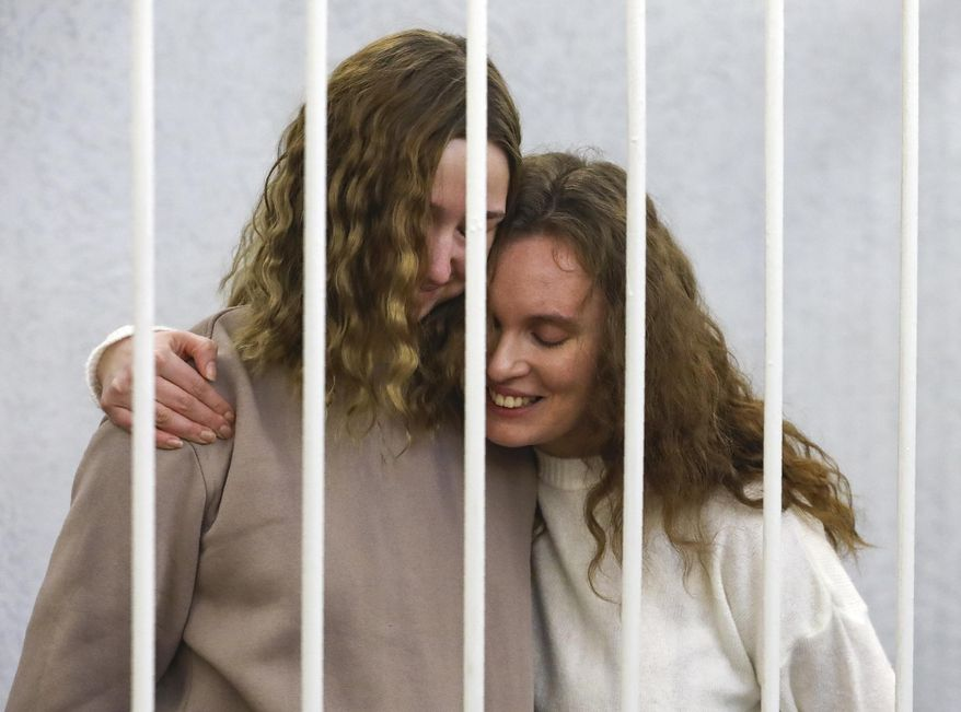 """Journalists Ekaterina Bakhvalova, right, and Daria Chultsova embrace inside a defendants' cage during a court hearing in Minsk, Belarus, Tuesday, Feb. 9, 2021. A court in Belarus on Tuesday opened a trial of two journalists, who could face years in prison after covering a protest. Ekaterina Bakhvalova and Daria Chultsova were filming police action to disperse a protest in the Belarusian capital, Minsk, in November for Belsat TV channel when they were arrested and charged of """"organizing actions rudely violating public order."""" They denied the accusations. (AP Photo)"""
