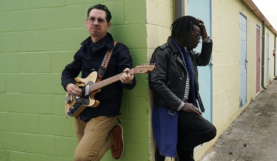 """Adrian Quesada, right, and Eric Burton, of Black Pumas, pose for a portrait in Austin, Texas on Feb. 5, 2021. Their deluxe debut album is nominated for album of the year at the 2021 Grammy Awards and their single """"Colors"""" is nominated for record of the year and best American roots performance.  (AP Photo/Eric Gay)"""