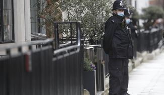 Police officers stand outside King Edward VII's hospital in London, Thursday, Feb. 18, 2021. Buckingham Palace says 99-year-old Prince Philip has been admitted to a London hospital after feeling unwell. The palace said the husband of Queen Elizabeth II was admitted to the private King Edward VII Hospital on Tuesday evening. (AP Photo/Kirsty Wigglesworth)