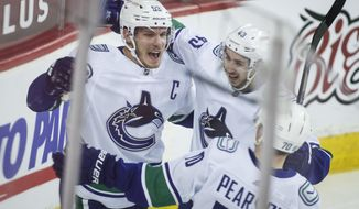 Vancouver Canucks' Bo Horvat, left, celebrates his goal with teammates during the second period of an NHL hockey game against the Calgary Flames on Wednesday, Feb. 17, 2021, in Calgary, Alberta. (Jeff McIntosh/The Canadian Press via AP)