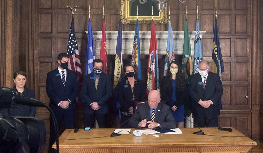 Montana Gov. Greg Gianforte, center, signs HB102 on Thursday, Feb. 18. 2021, in the State Capitol in Helena, Mont. The bill allows concealed firearms to be carried in most places in the state without a permit, and expands the list of places where guns can be carried to include university campuses and the state Capitol. (AP Photo/Iris Samuels)
