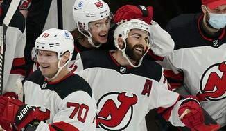 New Jersey Devils right wing Kyle Palmieri, second from right, celebrates his goal with teammates Jack Hughes (86) and Dmitry Kulikov (70) in the second period of an NHL hockey game against the Boston Bruins, Thursday, Feb. 18, 2021, in Boston. (AP Photo/Elise Amendola)