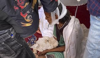 An elderly woman who fled to the city of Axum in the Tigray region of Ethiopia to seek safety sits with her head bandaged after being wounded during an attack on the city, Monday, Nov. 30, 2020. She later died of her wounds. As Ethiopia's Tigray region slowly resumes telephone service after three months of conflict, witnesses gave The Associated Press a detailed account of what might be its deadliest massacre, at the sacred Ethiopian Orthodox church in Axum. (AP Photo)