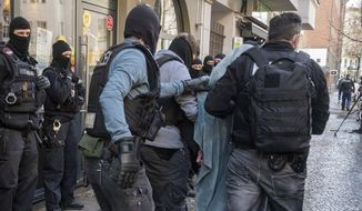 A man is led away by police with a blanket over his head during a raid in Berlin, Germany, Thursday, Feb. 18, 2021. Police cracked down on clan crime in Berlin and the surrounding area with a major raid on Thursday morning. (Christophe Gateau/dpa via AP)