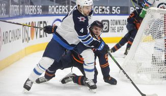Edmonton Oilers' Connor McDavid (97) and Winnipeg Jets' Neal Pionk (4) vie for the puck during the second period of an NHL hockey game Wednesday, Feb. 17, 2021, in Edmonton, Alberta. (Jason Franson/The Canadian Press via AP)