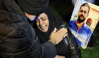 A mother of a victim of the Aug. 4, 2020 Beirut port explosion reacts next of a portrait of her son who killed during the explosion, during a sit-in outside the Justice Palace, in Beirut, Lebanon, Thursday, Feb. 18, 2021. Lebanon's highest court asked the chief prosecutor investigating last year's massive Beirut port explosion to step down, following legal challenges by senior officials he had accused of negligence that led to the blast, a judicial official and the country's official news agency said. (AP Photo/Hussein Malla)
