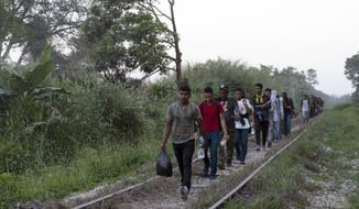 Migrants walk on train tracks on their journey from Central America to the U.S. border., in Palenque, Chiapas state, Mexico, Wednesday, Feb. 10, 2021. (AP Photo/Isabel Mateos)