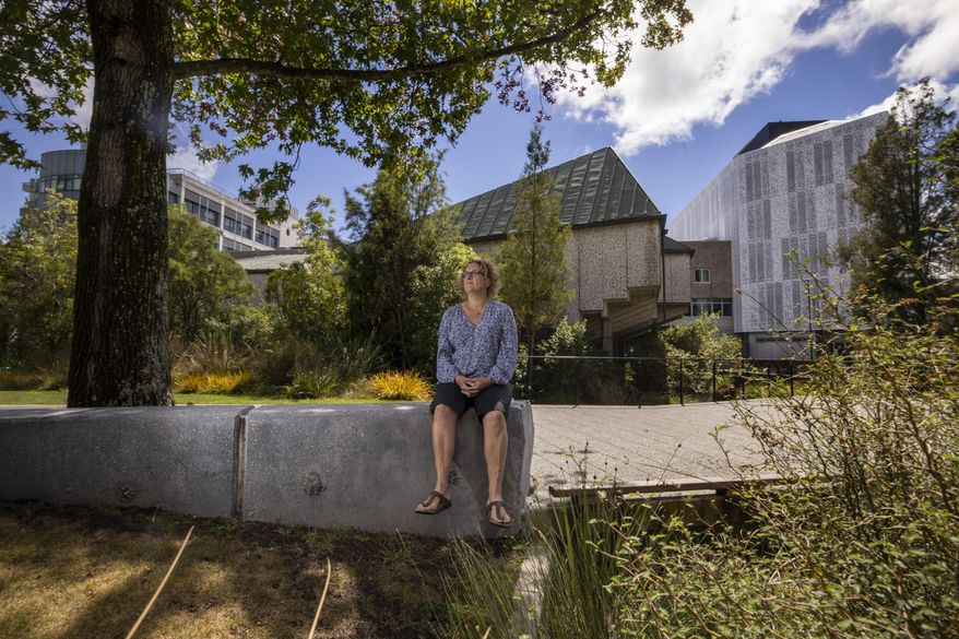 Ann Brower, the lone survivor from a bus which was hit by falling debris from a building during the Christchurch earthquake 10 years ago, sits at her workplace in Christchurch, New Zealand, Wednesday, Feb. 10, 2021. One woman has used her anger to ensure buildings are safer. Others have found peace after heartbreaking losses. Ten years after the earthquake in Christchurch killed 185 people and devastated the city, some of those profoundly affected are sharing their journeys. (AP Photo/Peter Meecham)