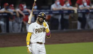 FILE - In this Oct. 1, 2020, file photo, San Diego Padres' Fernando Tatis Jr. tosses his bat after hitting a two-run home run during the seventh inning of Game 2 of the team's National League wild-card baseball series against the St. Louis Cardinals in San Diego. Tatis Jr. has yet to take a ground ball or swing a bat at spring training and he i already the talk of the Padres' clubhouse. The electrifying shortstop and the Padres have agreed to a $340 million, 14-year deal, giving San Diego's camp even more buzz than it already had after the team made a number of high-profile offseason moves. (AP Photo/Gregory Bull, File)