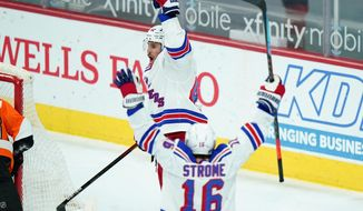 New York Rangers' Brendan Smith, top and Ryan Strome celebrate after Smith's goal during the third period of an NHL hockey game against the Philadelphia Flyers, Thursday, Feb. 18, 2021, in Philadelphia. (AP Photo/Matt Slocum)