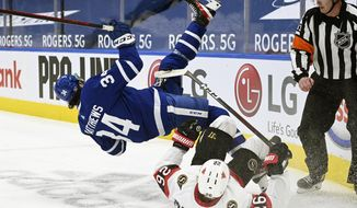 Toronto Maple Leafs center Auston Matthews (34) falls over Ottawa Senators defenseman Erik Brannstrom (26) during the first period of an NHL hockey game, Thursday, Feb. 18, 2021 in Toronto. (Nathan Denette/The Canadian Press via AP)