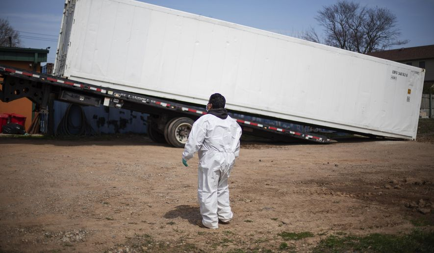 In this Tuesday, April 7, 2020, file photo, gravedigger Thomas Cortez watches as a refrigerated trailer is delivered to keep pace with a surge of bodies arriving for burials, mostly those who died from coronavirus, at the Hebrew Free Burial Association's cemetery in the Staten Island borough of New York. (AP Photo/David Goldman) ** FILE **
