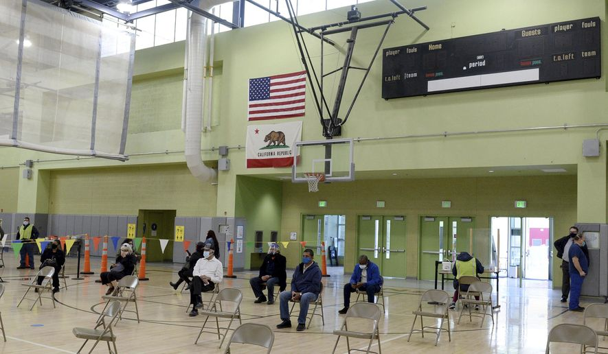 Los Angeles Unified School District employees wait in the school gym before getting their first dose of the Moderna vaccine, as LAUSD's first vaccination site opened at the Roybal Learning Center, Wednesday, Feb. 17, 2021, in Los Angeles. Superintendent Austin Beutner was there in the morning to meet with the vaccination team and the first district employees to receive their vaccines at this site. (Dean Musgrove/The Orange County Register/SCNG via AP)