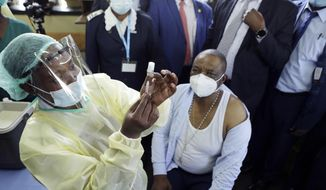 A nurse prepares to give a shot of China's Sinopharm vaccine to Zimbabwean Deputy President Constatino Chiwenga, right, at local hospital in Harare, Thursday, Feb, 18, 2021. Chiwenga become the first person in the country to receive the jab marking the first phase of the country's vaccination campaign. (AP Photo/Tsvangirayi Mukwazhi)