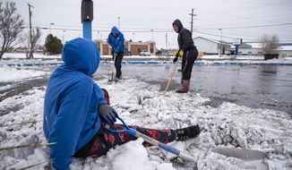 """Mighty Wash employee Fuastino """"Frosty"""" Calderon watches his coworkers shovel the car wash's driveway from atop a pile of snow after slipping on ice Wednesday, Feb. 17, 2021 in Odessa, Texas. Calderon and his coworkers shoveled snow at the car wash on Wednesday as a way to help pass the time and keep from being stuck inside as the Permian Basin begins to recover from the severe winter storm that passed through Texas. (Eli Hartman/Odessa American via AP)"""