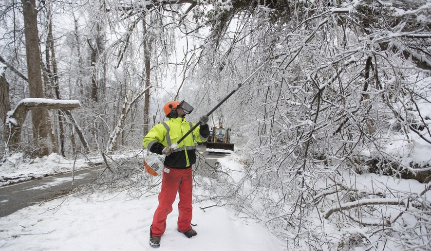 Michael Reynolds with the West Virginia Department of Highways works to clear tree limbs from utility lines along McCullough Road after an overnight snow piled on already ice-damaged areas on Thursday, Feb. 18, 2021, in Huntington, W.Va. (Sholten Singer/The Herald-Dispatch via AP)