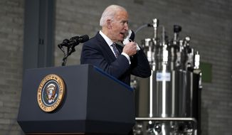 President Joe Biden removes his face masks as he prepares to speak after a tour of a Pfizer manufacturing site, Friday, Feb. 19, 2021, in Portage, Mich. (AP Photo/Evan Vucci)