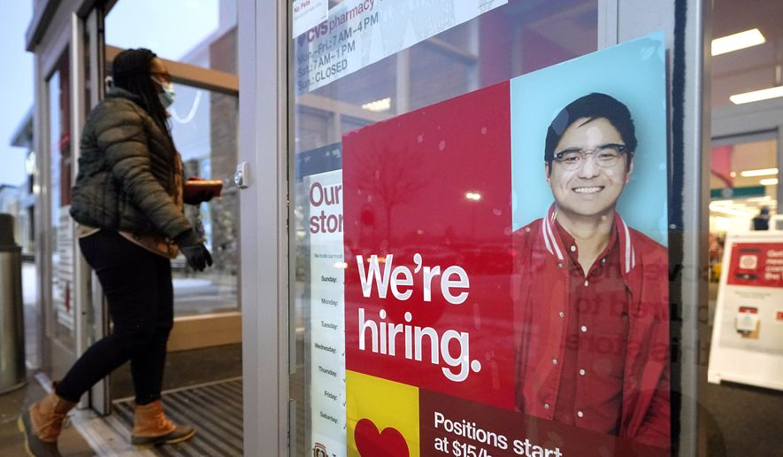 In this Feb. 9, 2021, file photo, a passer-by walks past an employment hiring sign while entering a Target store location, in Westwood, Mass. (AP Photo/Steven Senne, File)