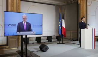 French President Emmanuel Macron, right, attends a video-conference meeting as U.S. President Joe Biden appear on a screen ahead of a 2021 Munich Security Conference at the Elysee palace in Paris, Friday Feb. 19, 2021. (Benoit Tessier/Pool via AP)