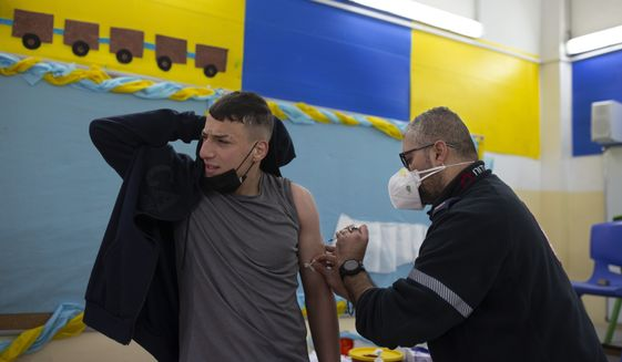 A Palestinian youth reacts as a medic with the Magen David Adom emergency service administers a dose of the Pfizer-BioNTech COVID-19 vaccine during a one-day clinic at a school near the Al Aqsa Mosque compound to vaccinate worshippers following Friday prayers in the Old City of Jerusalem, Friday, Feb. 19, 2021. (AP Photo/Maya Alleruzzo)