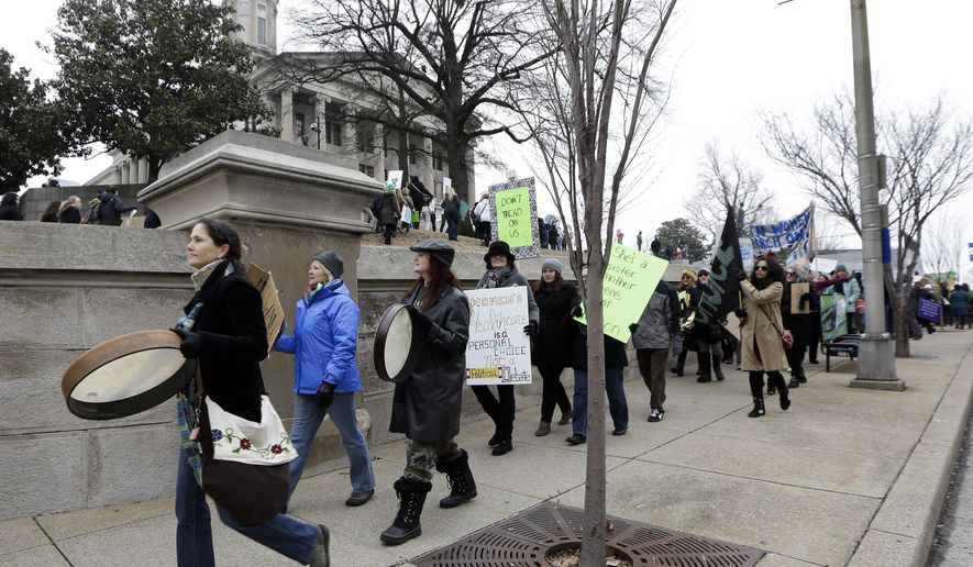 FILE - In this Tuesday, Jan. 13, 2015, file photo, pro-abortion rights protesters march to the Capitol on the opening day of the second session of the 109th General Assembly, in Nashville, Tenn. A federal court on Friday, Feb. 19, 2021, denied a request to keep Tennessee's 48-hour waiting period for abortions in effect while it hears an appeal of a lower court's ruling that found it unconstitutional. U.S. District Judge Bernard Friedman ruled in October that Tennessee's waiting period law serves no legitimate purpose while placing a substantial burden on women who seek abortions in Tennessee. (AP Photo/Mark Humphrey, File)