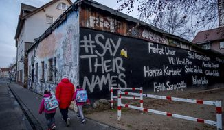 The names of the nine victims of the Hanau shooting are painted on a building in Hanau, Germany, Thursday, Feb.18, 2021. One year ago a far right man shot nine people before he shot himself. Hanau will commemorate the victims on Friday. (AP Photo/Michael Probst)