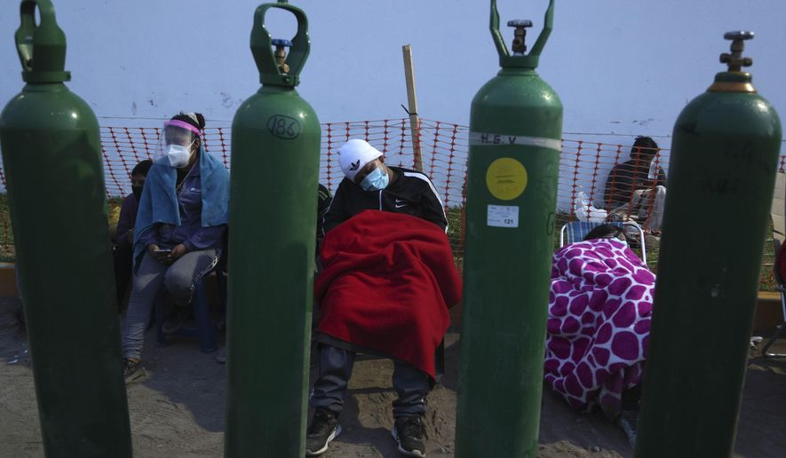 People sleep framed by their empty oxygen cylinders waiting for a shop to open to refill their tanks, in the Villa El Salvador neighborhood of Lima, early Thursday morning, Feb. 18, 2021, as the lack of medical oxygen to treat COVID-19 patients continues to be the norm in Peru. Long lines form outside private providers with many spending the night outside so as to not lose their place in line. (AP Photo/Martin Mejia)