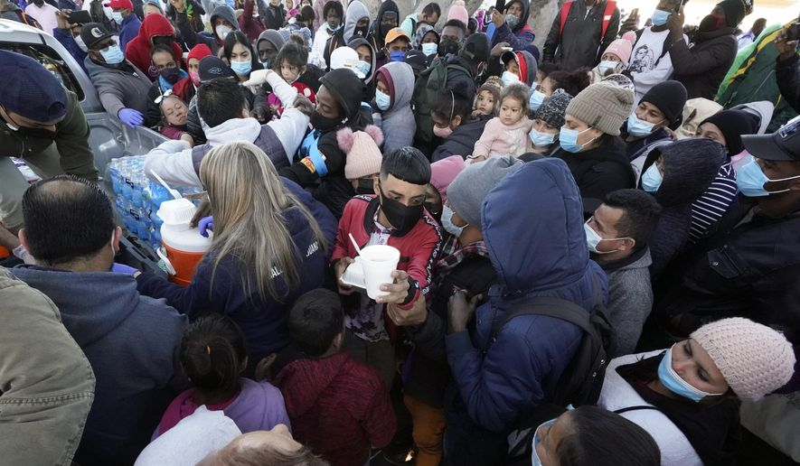 Asylum seekers receive food as they wait for news at the border, Friday, Feb. 19, 2021, in Tijuana, Mexico. (AP Photo/Gregory Bull) ** FILE **