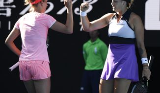 Belgium's Elise Mertens, left, and Aryna Sabalenka of Belarus gesture as they play against Barbora Krejcikova and Katerina Siniakova of the Czech Republic during the women's doubles final at the Australian Open tennis championship in Melbourne, Australia, Friday, Feb. 19, 2021.(AP Photo/Andy Brownbill)