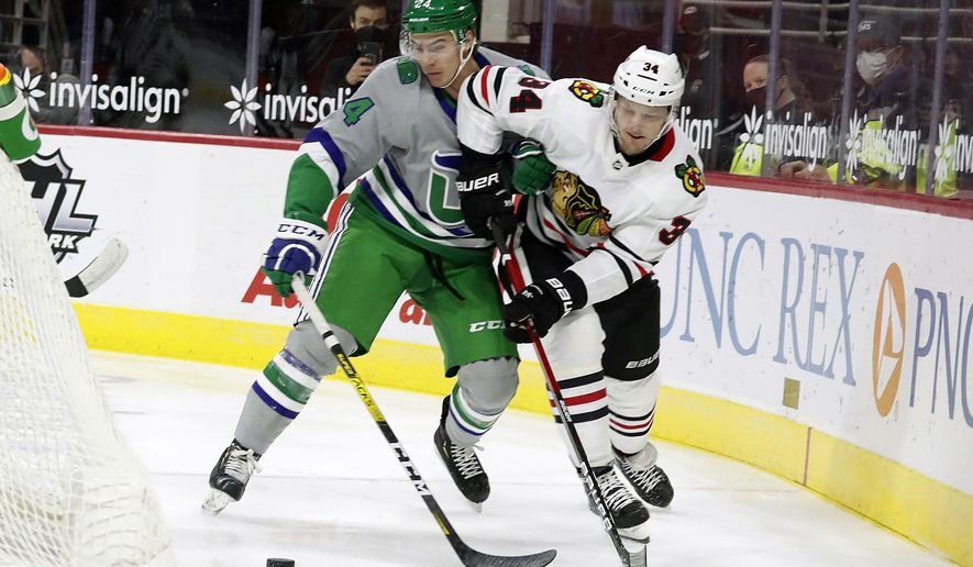 Carolina Hurricanes' Jake Bean (24) and Chicago Blackhawks' Carl Soderberg (34) battle for the puck during the first period of an NHL hockey game in Raleigh, N.C., Friday, Feb. 19, 2021. (AP Photo/Karl B DeBlaker)