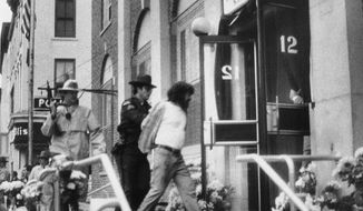 FILE - In this Oct. 24, 1981, file photo, David J. Gilbert, right, is escorted by police into the Village Hall in Nyack, N.Y., for a hearing on felony murder charges stemming from the Oct. 20, 1981, Brink's armored car robbery at a mall in Nanuet, N.Y., and a subsequent shootout with Nyack police that left three people dead. Now 76 years old, Gilbert, is still imprisoned in New York state after nearly four decades. Gilbert's son, San Francisco chief District Attorney Chesa Boudin, and other allies are lobbying for clemency for Gilbert as coronavirus cases rise among prison inmates. (AP Photo/David Handschuh, File)