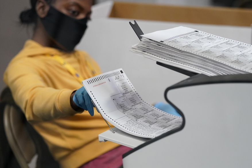 FILE - In this Nov. 5, 2020, file photo, a county election worker scans mail-in ballots at a tabulating area at the Clark County Election Department in Las Vegas. Nevada is asking a state court judge to throw out a lawsuit filed more than a month after the November election that claims voter rolls are rife with ineligible names and ballots cast by noncitizens diminish the value of votes by properly registered voters. (AP Photo/John Locher, File) **FILE**