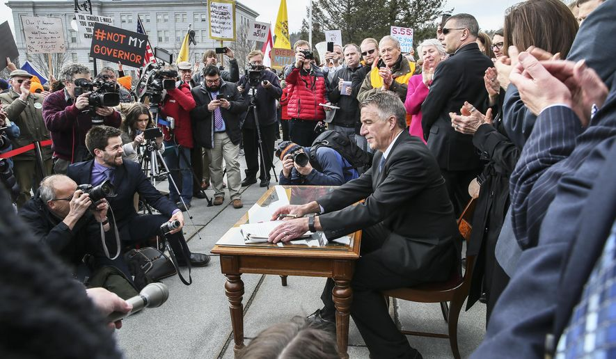 FILE - In this April 11, 2018 file photo, Vermont Gov. Phil Scott finishes signing a gun restrictions bill on the steps of the Statehouse in Montpelier, Vt. On Friday, Feb. 19, 2021, the Vermont Supreme Court upheld the legality of the portion of the 2018 legislation that restricts the size of large-capacity ammunition magazines for firearms. (AP Photo/Cheryl Senter, File)