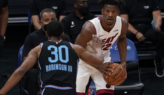 Sacramento Kings forward Glenn Robinson III, left, guards Miami Heat forward Jimmy Butler, right, during the first half of an NBA basketball game in Sacramento, Calif., Thursday, Feb. 18, 2021. (AP Photo/Rich Pedroncelli)
