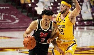 Nebraska's Trey McGowens (2) drives around Minnesota's Gabe Kalscheur (22) in the second half of an NCAA college basketball game, Monday, Feb. 8, 2021, in Minneapolis.  (AP Photo/Jim Mone)