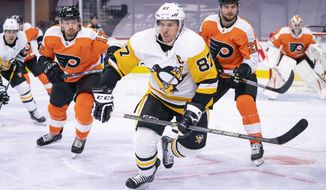 FILE - Pittsburgh Penguins' Sidney Crosby, center, heads after the puck after winning the face off against Philadelphia Flyers' Scott Laughton, right, with Michael Raffl, left, during the third period of an NHL hockey game in Philadelphia, in this Wednesday, Jan. 13, 2021, file photo. The Flyers won 6-3. A decade ago, Sidney Crosby's career was at a crossroads thanks to what became an extended absence due to a concussion. On the eve of his franchise-record 1000th regular season game, the superstar looks just as dangerous as ever, with no end in sight. (AP Photo/Chris Szagola, File)