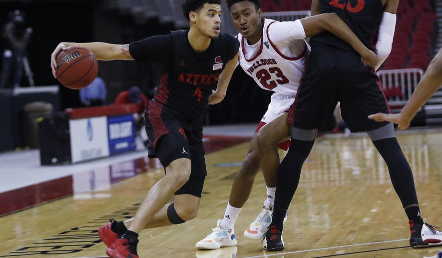 San Diego State's Trey Pulliam looks to drive past Fresno State's Leo Colimerio during the second half of an NCAA college basketball game in Fresno, Calif., Thursday, Feb. 18, 2021. (AP Photo/Gary Kazanjian)