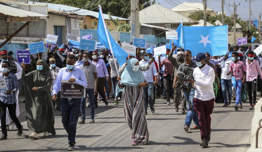 Somalis march and protest against the government and the delay of the country's election in the capital Mogadishu, Somalia Friday, Feb. 19, 2021. Security forces in Somalia's capital fired on hundreds of people protesting the delay of the country's election on Friday as at least one explosion was reported at the international airport and armored personnel carriers blocked major streets. (AP Photo)