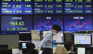 A currency trader talks with his colleague at the foreign exchange dealing room of the KEB Hana Bank headquarters in Seoul, South Korea, Friday, Feb. 19, 2021. Asian stock markets followed Wall Street lower on Friday after disappointing U.S. jobs and economic data. (AP Photo/Ahn Young-joon)
