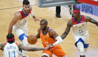 Phoenix Suns guard Chris Paul (3) drives the lane between New Orleans Pelicans guard Eric Bledsoe (5), center Willy Hernangomez (9) and forward Brandon Ingram (14) during the second half of an NBA basketball game in New Orleans, Friday, Feb. 19, 2021. (AP Photo/Gerald Herbert)