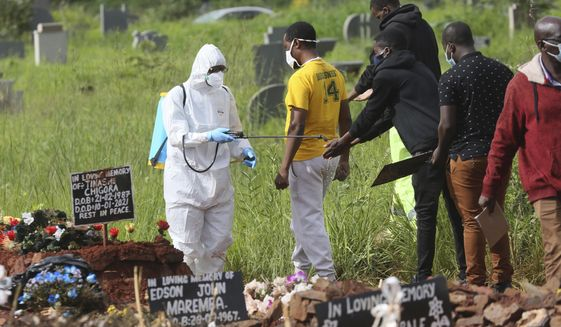 In this Jan. 15, 2021, file photo, a health worker disinfects family members during a burial of a person who died from COVID-19, in Harare, Zimbabwe. Africa has surpassed 100,000 confirmed deaths from COVID-19 as the continent praised for its early response to the pandemic now struggles with a dangerous resurgence and medical oxygen often runs desperately short. (AP Photo/Tsvangirayi Mukwazhi, File)