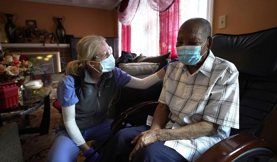 Geriatrician Megan Young, left, offers support to Edouard Joseph, 91, moments after giving him a COVID-19 vaccination, Thursday, Feb. 11, 2021, at his home in the Mattapan neighborhood of Boston. Millions of U.S. residents will need COVID-19 vaccines brought to them because they rarely or never leave home. Doctors and nurses who specialize in home care are leading this push and starting to get help from state and local governments around the country. (AP Photo/Steven Senne)