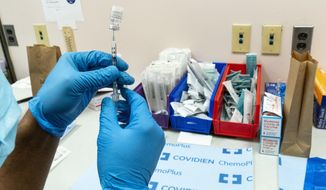 A pharmacist prepares a syringe with the Pfizer-BioNTech COVID-19 vaccine at a COVID-19 vaccination site at NYC Health + Hospitals Metropolitan, Thursday, Feb. 18, 2021, in New York. (AP Photo/Mary Altaffer)