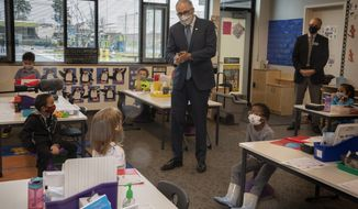 Washington Gov. Jay Inslee speaks with kindergartners in Chelsea Singh's class during a visit to Firgrove Elementary School in Puyallup, Wash., Thursday, Feb. 18, 2021. Students are back in school and all teachers and students are wearing masks. (Ellen M. Banner/The Seattle Times via AP, Pool)