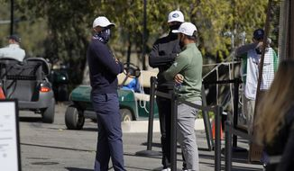 From left, Tiger Woods, Dustin Johnson and Xander Schauffele talk after wind suspended play during the third round of the Genesis Invitational golf tournament at Riviera Country Club, Saturday, Feb. 20, 2021, in the Pacific Palisades area of Los Angeles. (AP Photo/Ryan Kang) **FILE**
