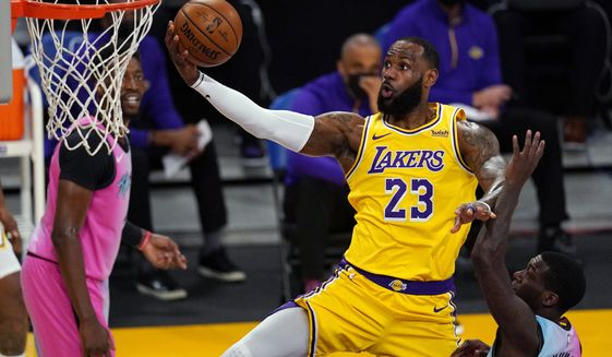 Los Angeles Lakers forward LeBron James shoots as Miami Heat guard Kendrick Nunn, right, defends during the first half of an NBA basketball game Saturday, Feb. 20, 2021, in Los Angeles. (AP Photo/Mark J. Terrill)