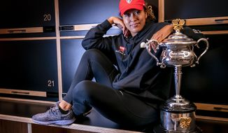 Japan's Naomi Osaka poses with the Daphne Akhurst Memorial Cup in the locker room in the early hours of Sunday Feb. 21, 2021 after defeating United States Jennifer Brady in the women's singles final at the Australian Open tennis championship in Melbourne, Australia, Saturday, Feb. 20, 2021.(Fiona Hamilton/Tennis Australia via AP)