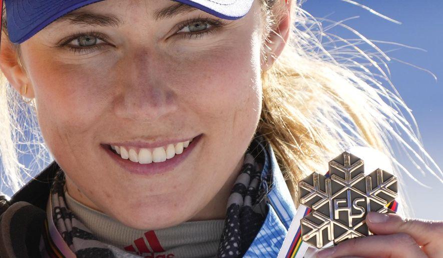 United States' Mikaela Shiffrin shows her bronze medal of the women's slalom, at the alpine ski World Championships in Cortina d'Ampezzo, Italy, Saturday, Feb. 20, 2021. (AP Photo/Giovanni Auletta)