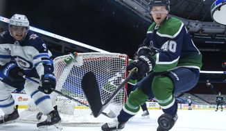 Vancouver Canucks' Elias Pettersson (40) reaches for the puck in front of Winnipeg Jets' Andrew Copp (9) during the second period of an NHL hockey game Friday, Feb. 19, 2021, in Vancouver, British Columbia. (Darryl Dyck/The Canadian Press via AP)