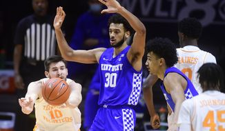 Tennessee's John Fulkerson (10) passes the ball as Kentucky's Olivier Sarr (30) defends during an NCAA college basketball game Saturday, Feb. 20, 2021, in Knoxville, Tenn. (Caitie McMekin/Knoxville News Sentinel via AP, Pool)